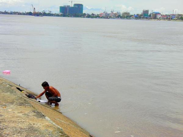 Widok na Mekong niedaleko Pałacu Królewskiego w centrum Phnom Penh. W kadrze widać mężczyznę, który prał w Mekongu swoje ubrania, a także zażywał kąpieli. Po chwili dołączył do niego jego młodszy brat.