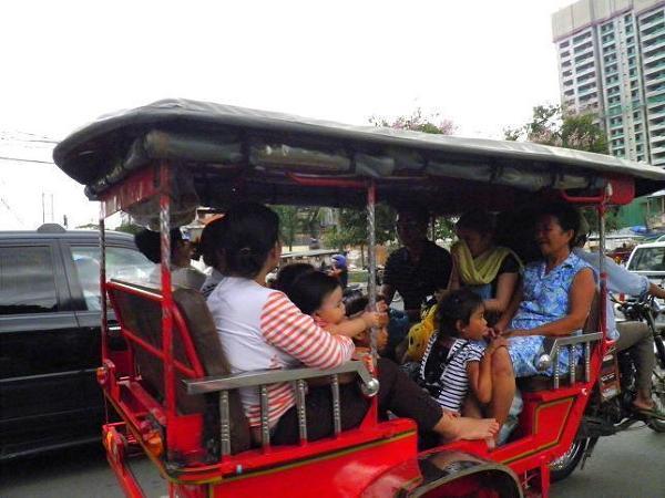 Tuk-tuk. Niewielkie rozmiary Khmerów przydają się podczas zbiorczego przemieszczania się między innymi tuk-tukiem. Na zdjęciu z Phnom Penh trzynastu! (choć wszystkich nie widać) Khmerów w jednym! tuk-tuku, gdzie normalnie mieści się 4 Europejczyków.
