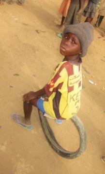 """Chłopiec z N'djameny. Popularna zabawa """"toczenie opony"""""""