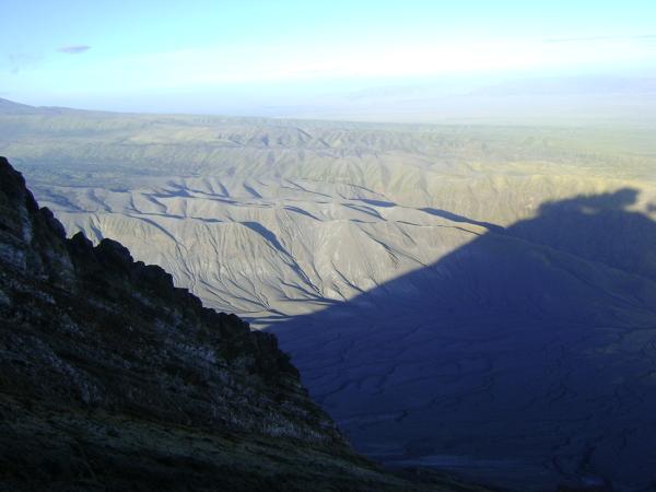 Rów widziany ze zbocza Lengai, na którym kładzie się cień wulkanu z wyraźnymi oparami siarki.