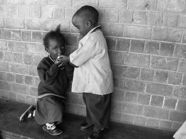 Przedszkolaki przynoszą z domu drugie śniadanie. Niestety niektóre przychodzą z pustymi plecakami, dlatego dzieci uczone są dzielenia się tym co posiadają. Na zdjęciu mały Maenza karmi ciastkiem Miriam.