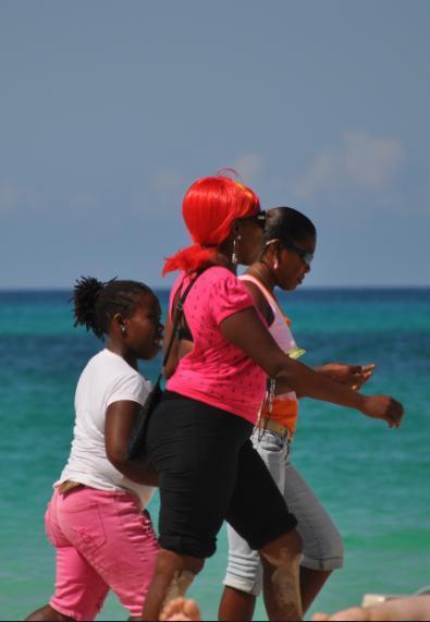 """Plaża w Negrilu, Jamajka. Kobiety na wyspie noszą skomplikowane i wielobarwne fryzury, doskonale utrzymane żelem. Stroje wahają się od sugestywnych do jawnie """"tylko dla dorosłych"""". Jamajczycy uwielbiają przyozdabiać się ciężką, złotą biżuterią i nosić jaskrawe ciuchy."""