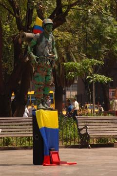 Partyzant FARC zarabia na życie na placu Botero w Medellin.