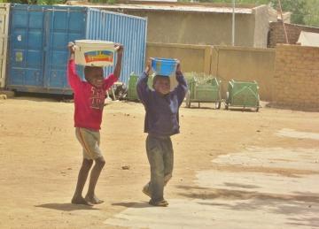 Dzieci niosące wodę ze studni.